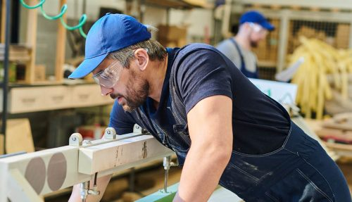 Serious concentrated handsome young furniture worker in safety goggles standing at assembling machine and fixing wooden plank on it